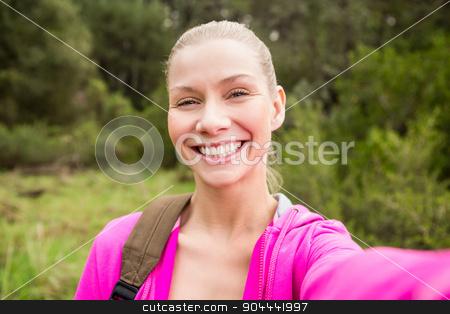 Smiling female hiker taking a selfie stock photo, Portrait of a smiling female hiker taking a selfie in the nature by Wavebreak Media