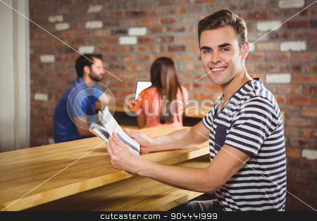 Young man reading a newspaper stock photo,  Portrait of young man reading a newspaper in a coffee shop by Wavebreak Media