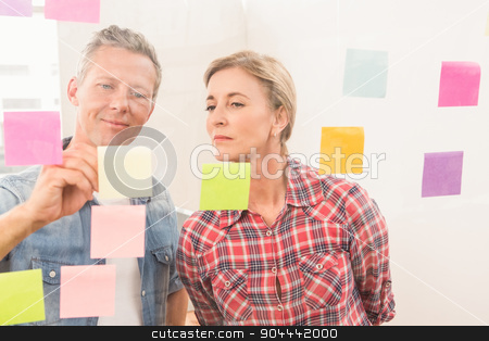 Casual business colleagues writing on sticky notes stock photo, Casual business colleagues writing on sticky notes in the office by Wavebreak Media