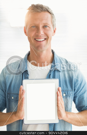 Smiling businessman showing up his tablet stock photo, Portrait of a smiling businessman showing up his tablet at office by Wavebreak Media