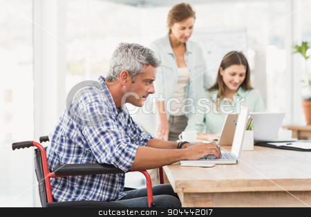 Casual businessman in wheelchair using laptop stock photo, Casual businessman in wheelchair using laptop in the office by Wavebreak Media
