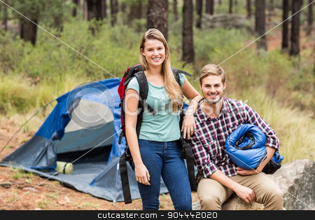 Portrait of a young pretty hiker couple holding a sleeping bag a stock photo, Portrait of a young pretty hiker couple holding a sleeping bag and backpack in the nature by Wavebreak Media
