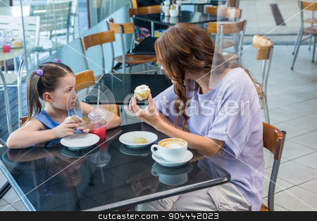 Mother and daughter enjoying cakes stock photo, Mother and daughter enjoying cakes in coffee shop by Wavebreak Media