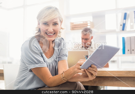 Smiling businesswoman scrolling on a tablet stock photo, Portrait of a smiling businesswoman scrolling on a tablet at office by Wavebreak Media