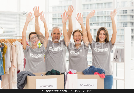 Cheering volunteers holding arms up stock photo, Portrait of cheering volunteers holding arms up in the office by Wavebreak Media