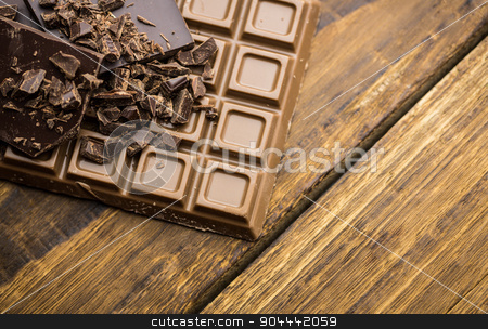 Dark and milk chocolate on a wooden table stock photo, Close up view of dark and milk chocolate on a wooden table by Wavebreak Media