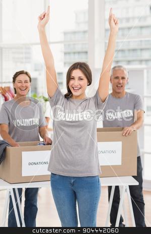 Cheering female volunteer in front of colleagues stock photo, Portrait of cheering female volunteer in front of colleagues in the office by Wavebreak Media