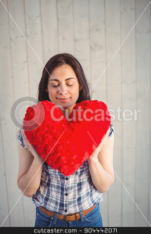 Pretty hipster holding heart pillow stock photo, Pretty hipster holding heart pillow on wooden planks background by Wavebreak Media