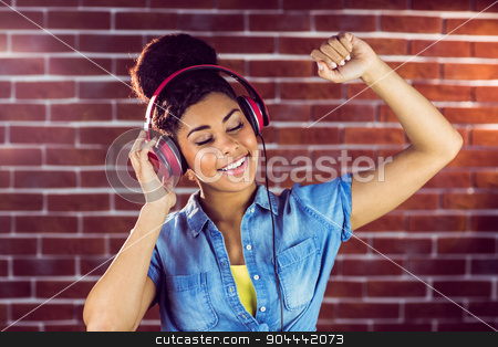 A smiling woman dancing with headphones stock photo, A smiling woman dancing with headphones on a brick wall by Wavebreak Media