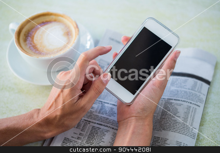 Woman having cappuccino using her phone stock photo, Woman having cappuccino using her phone in a cafe by Wavebreak Media