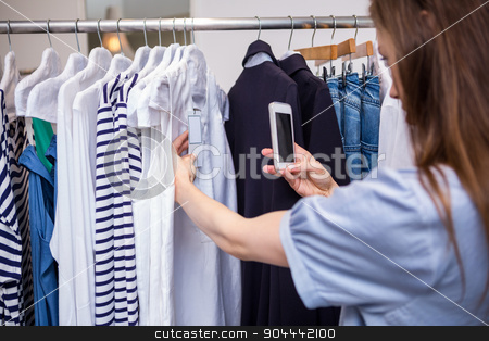 Woman taking a photo of price tag stock photo, Woman taking a photo of price tag in fashion boutique by Wavebreak Media