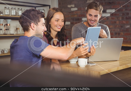 Smiling friends pointing and looking at tablet computer stock photo, Smiling friends pointing and looking at tablet computer at coffee shop by Wavebreak Media