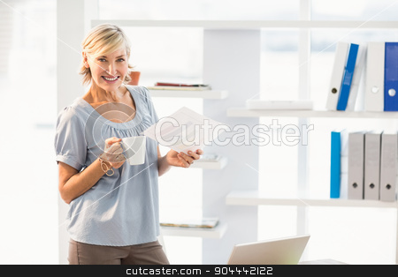 Smiling businesswoman holding a document stock photo, Portrait of a smiling businesswoman holding a document at office by Wavebreak Media