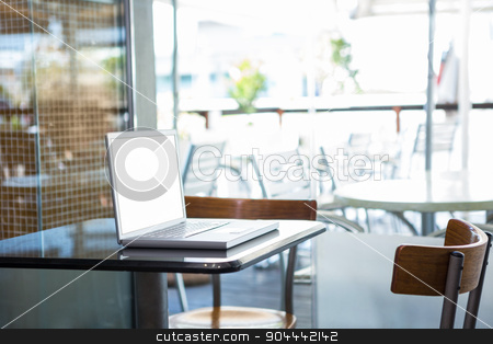 Laptop on a table stock photo, Laptop on a table in a coffee shop by Wavebreak Media
