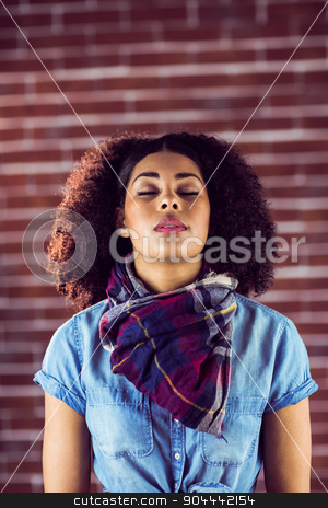 Attractive young woman with eyes closed stock photo, Attractive young woman with eyes closed against red brick background by Wavebreak Media