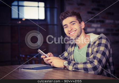 Smiling hipster using smartphone stock photo, Portrait of smiling hipster using smartphone at coffee shop by Wavebreak Media