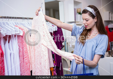Brunette woman shopping for clothes stock photo, Brunette woman shopping for clothes in fashion boutique by Wavebreak Media