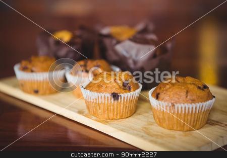 Chocolate chip muffins on cutting board stock photo, Chocolate chip muffins on cutting board at coffee shop by Wavebreak Media