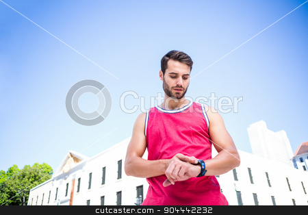 Handsome athlete adjusting his stopwatch stock photo, Handsome athlete adjusting his stopwatch on a sunny day by Wavebreak Media