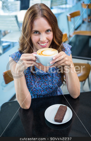 Pretty brunette having coffee and cake stock photo, Pretty brunette having coffee and cake in a coffee shop by Wavebreak Media