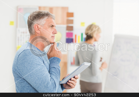Thoughtful businessman holding a digital tablet stock photo, Thoughtful businessman holding a digital tablet at the office by Wavebreak Media