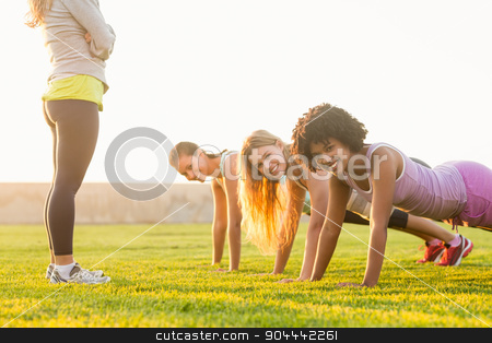 Smiling sporty women doing push ups during fitness class stock photo, Portrait of smiling sporty women doing push ups during fitness class in parkland by Wavebreak Media