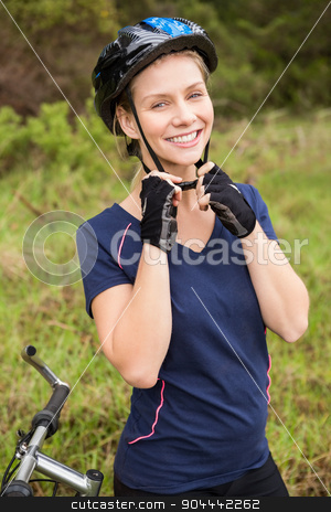 Smiling athletic blonde putting on helmet  stock photo, Portrait of smiling athletic blonde putting on helmet in the nature by Wavebreak Media