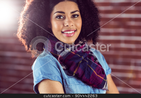 Attractive young woman smiling stock photo, Portrait of attractive young woman smiling against red brick background by Wavebreak Media