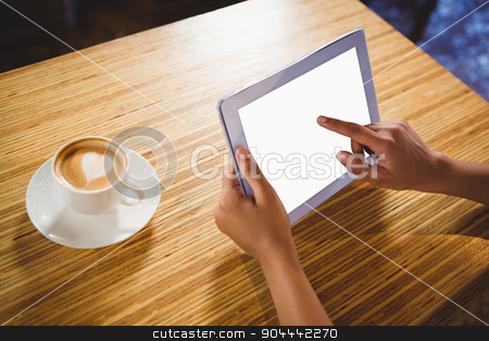 A businesswoman using a tablet and enjoying a coffee stock photo, A businesswoman using a tablet and enjoying a coffee in a cafe by Wavebreak Media