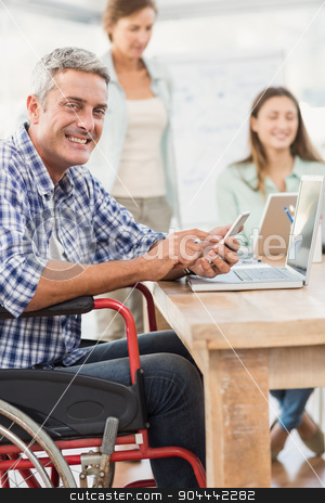 Casual businessman in wheelchair with smartphone stock photo, Portrait of casual businessman in wheelchair with smartphone in the office by Wavebreak Media