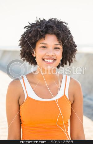 Young sporty woman enjoying music via headphones stock photo, Portrait of young sporty woman enjoying music via headphones at promenade by Wavebreak Media