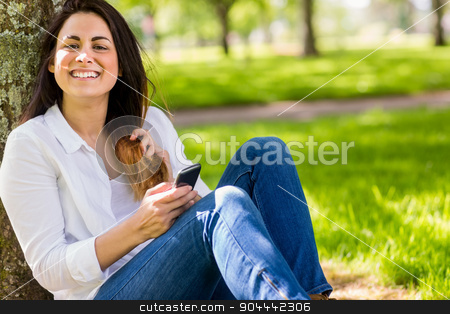 Beautiful brunette sending text in the park stock photo, Beautiful brunette sending text in the park on a sunny day by Wavebreak Media