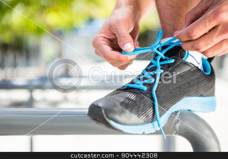 Athlete tying his shoes stock photo, Athlete tying his shoes in the city by Wavebreak Media