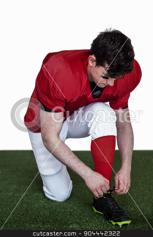 American football player tying his shoelaces stock photo, American football player tying his shoelaces on the field by Wavebreak Media