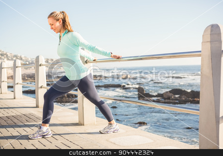 Fit blonde stretching on railing stock photo, Fit blonde stretching on railing at promenade by Wavebreak Media