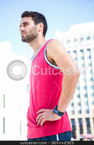 Serious handsome athlete with hands on hips stock photo, Side view of a handsome athlete with hands on hips on a sunny day by Wavebreak Media
