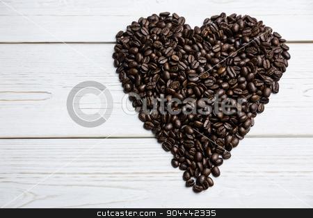 Coffee beans on a table in heart shape stock photo, Coffee beans on a table in heart shape shot in studio by Wavebreak Media