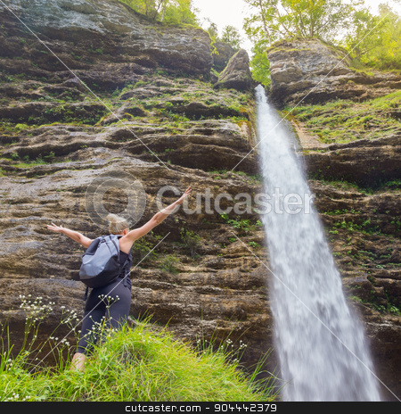Active sporty woman relaxing in beautiful nature. stock photo, Female hiker raising arms inhaling fresh air, feeling relaxed and free in beautiful natural environment under Pericnik waterfall in Vrata Valley in Triglav National Park in Julian Alps, Slovenia. by kasto