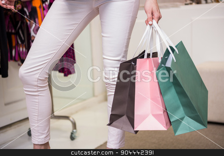 Woman standing with shopping bags stock photo, Woman standing with shopping bags in fashion boutique by Wavebreak Media