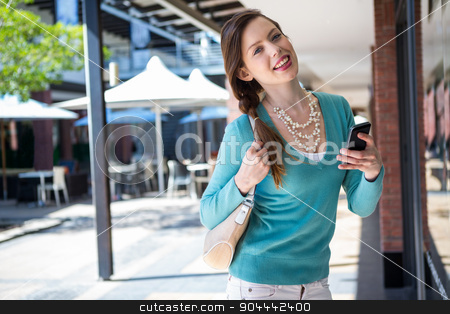 Brunette sending a text in the mall stock photo, Brunette sending a text in the mall on a sunny day by Wavebreak Media