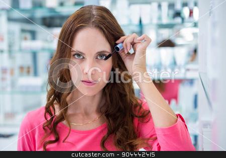 Pretty woman trying a mascara stock photo, Pretty woman trying a mascara at the pharmacy by Wavebreak Media