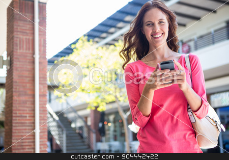 Pretty woman texting at the mall stock photo, Pretty woman texting at the mall on a sunny day by Wavebreak Media