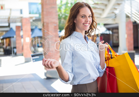Pretty woman shopping at the mall with card stock photo, Pretty woman shopping at the mall with card on a sunny day by Wavebreak Media