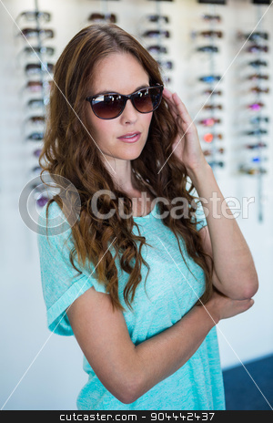 Pretty woman shopping for sunglasses stock photo, Pretty woman shopping for sunglasses at the optometry store by Wavebreak Media