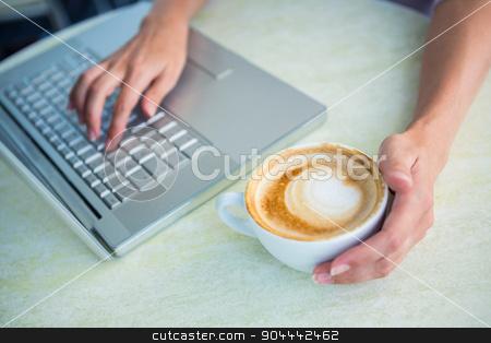 Woman enjoying a cappuccino using laptop stock photo, Woman enjoying a cappuccino using laptop at a cafe by Wavebreak Media