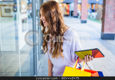 Pretty woman shopping at the mall using tablet stock photo, Pretty woman shopping at the mall using tablet on a sunny day by Wavebreak Media