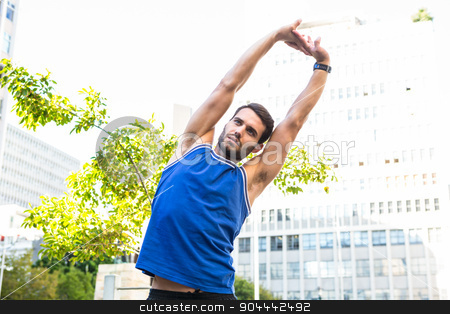 Handsome athlete stretching  stock photo, Handsome athlete stretching in the city by Wavebreak Media