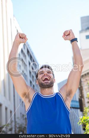 Happy handsome athlete triumphing stock photo, Happy handsome athlete triumphing in the city by Wavebreak Media