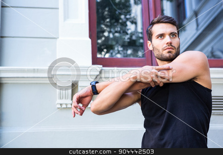 Handsome athlete stretching his arm stock photo, Handsome athlete stretching his arm in the city by Wavebreak Media