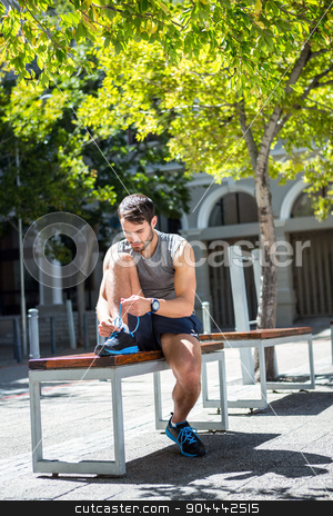 Handsome athlete tying shoelaces on a bench stock photo, Handsome athlete tying shoelaces on a bench on a sunny day by Wavebreak Media